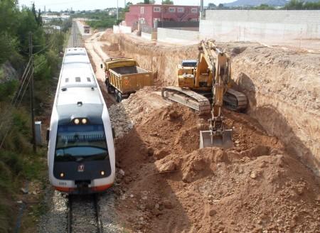 Her passerer toget medan arbeidaranene grev ny trasé til det nye sporet.